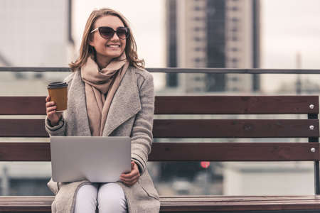 Photo pour Beautiful girl in coat and sun glasses is drinking coffee, using a laptop and smiling while sitting on a bench outdoors - image libre de droit