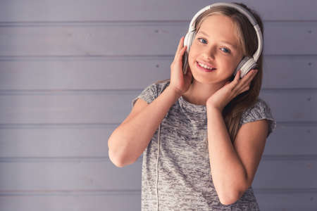Foto de Attractive teenage girls in headphones is listening to music, looking at camera and smiling, on gray wall background - Imagen libre de derechos
