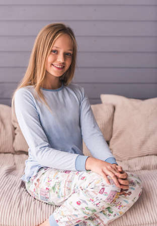 Foto de Attractive teenage girls in pajama is looking at camera and smiling while sitting on couch at home - Imagen libre de derechos