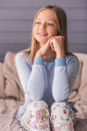 Photo pour Attractive teenage girls in pajama is looking away and smiling while sitting on couch at home - image libre de droit
