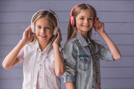 Photo for Two attractive teenage girls in headphones are listening to music, looking at camera and smiling, on gray wall background - Royalty Free Image