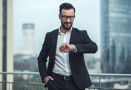 Foto de Handsome businessman in suit and glasses is looking at his watch and smiling while standing on the balcony - Imagen libre de derechos