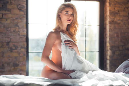 Foto de Naked blonde woman is covering her body with a blanket and looking sensually at camera while sitting on bed - Imagen libre de derechos