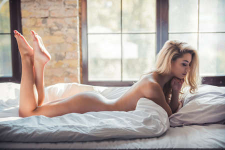 Photo for Naked blonde woman is lying on bed, sunshine on her body - Royalty Free Image