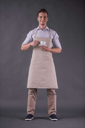 Foto de Full-length image of handsome young barista in apron holding a cup, looking at camera and smiling, on gray background - Imagen libre de derechos
