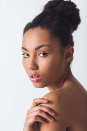 Photo for Beautiful Afro-American girl is touching her bare shoulder and looking at camera, isolated on white - Royalty Free Image