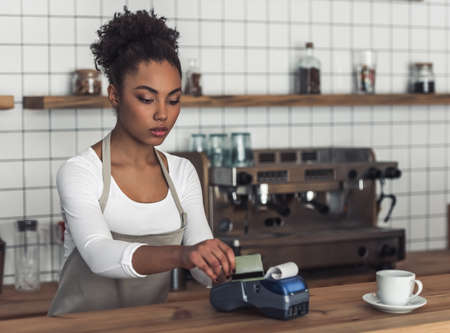 Foto de Beautiful Afro American barista in apron is using a payment terminal while standing at bar counter - Imagen libre de derechos
