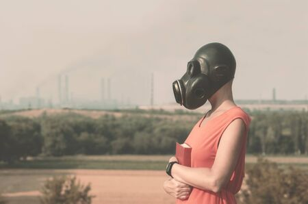 Photo for young girl in a gas mask in a red dress with a book in her hands against the background of smoking factory chimneys - Royalty Free Image
