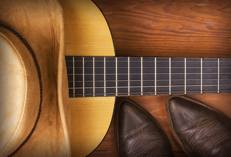 Photo pour American Country music with guitar and cowboy shoes on wood background - image libre de droit