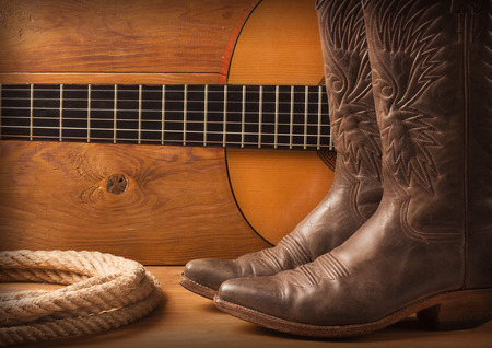 Photo pour Country music with guitar and cowboy shoes on wood texture background - image libre de droit