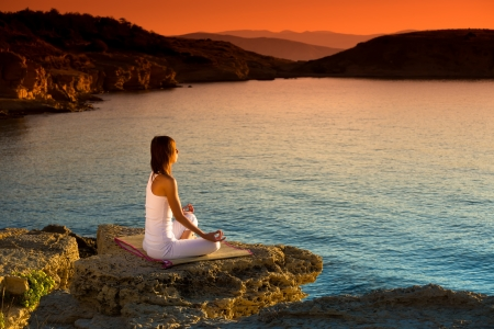 Photo pour Attractive young woman in a yoga position on a beautiful beach - image libre de droit