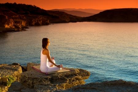 Foto de Attractive young woman in a yoga position on a beautiful beach - Imagen libre de derechos