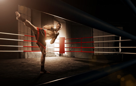 Photo pour Young  man kickboxing in the Arena - image libre de droit