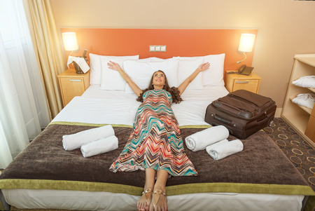 Photo for Young woman lying in the bed of a hotel room - Royalty Free Image