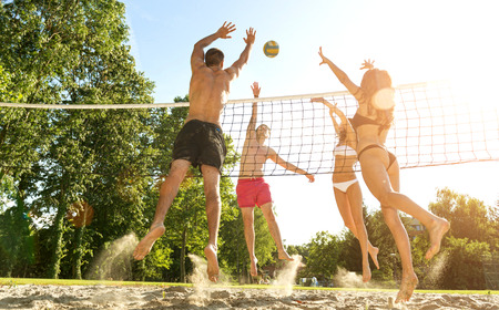Photo for Group young  Friends Playing Volleyball On Beach - Royalty Free Image