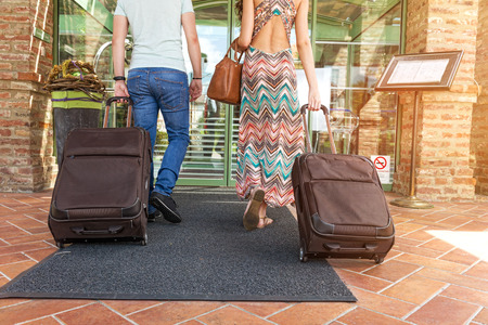 Photo for Young couple standing at hotel corridor upon arrival, looking for room, holding suitcases - Royalty Free Image