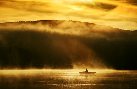 Photo for Early morning sunrise, boating on the lake in the sunlight - Royalty Free Image