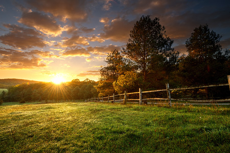 Foto de Picturesque landscape, fenced ranch at sunrise - Imagen libre de derechos