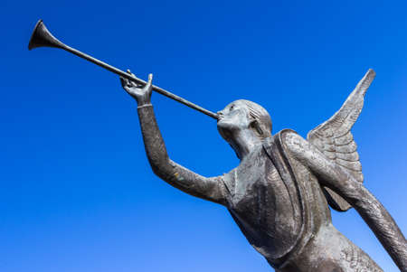 Photo for Statue of an angel playing a trumpet over blue sky - Royalty Free Image