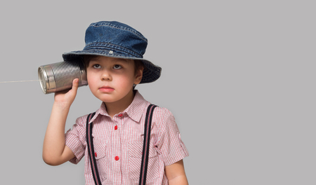Photo for A small boy attached a telephone from a tin can to his ear - Royalty Free Image