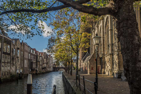 Photo for Voorstraatshaven and Grote Kerk in Dordrecht, Netherlands on a sunny afternoon. The trees have autumn colors and the sky is blue with clouds. - Royalty Free Image