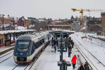 Foto per Naestved Denmark - March 1. 2018: Train at the platform at Naestved train station in Denmark with people waiting for another train - Immagine Royalty Free