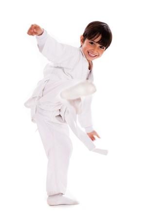 Karate kid kicking over isolated white background