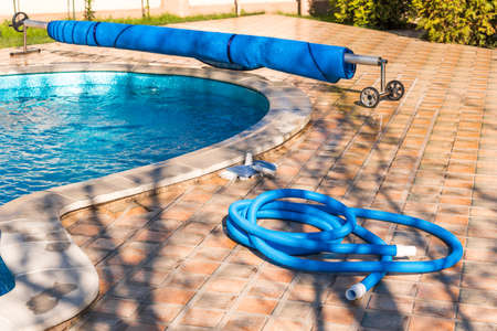 Photo pour Manual equipment for cleaning pool, brush, hose, swimming pool cover, Yesulskaya, Krasnodar, Russia. Copy space for text - image libre de droit