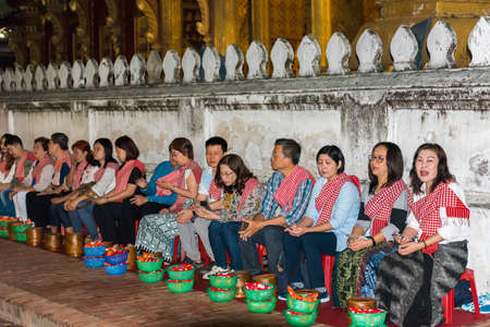 Photo for LUANG PRABANG, LAOS - JANUARY 11, 2017: Feeding the monks. The ritual is called Tak Bat. Copy space for text - Royalty Free Image