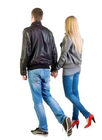 going young couple (man and woman) Back view  . walking beautiful friendly girl and guy in jacket and jeans together. Rear view people collection.  backside view of person.  Isolated over white background.