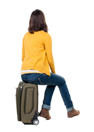 Photo for back view of walking  woman  in cardigan sits on a suitcase. beautiful  girl in motion.  backside view of person.  Rear view people collection. Isolated over white background. - Royalty Free Image