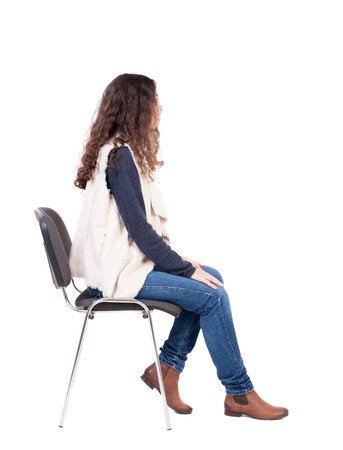 Photo pour back view of young beautiful  woman sitting on chair.  girl  watching. Rear view people collection.  backside view of person.  Isolated over white background. A girl in a white tank top sitting on a stool and looking to the right. - image libre de droit