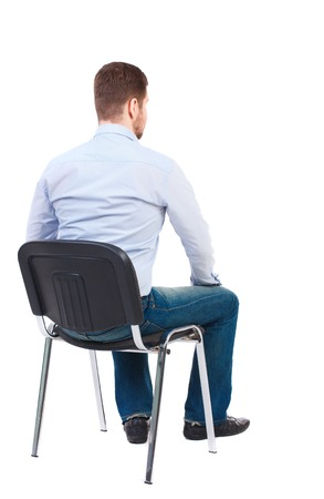 Photo pour back view of business man sitting on chair.  businessman watching. Rear view people collection.  backside view of person.  Isolated over white background. Bearded businessman in white shirt sits on a chair and looking forward. - image libre de droit