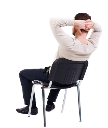 Foto de back view of business man sitting on chair. bearded man in a white warm sweater sits on a chair with his hands behind his head. Side view. - Imagen libre de derechos
