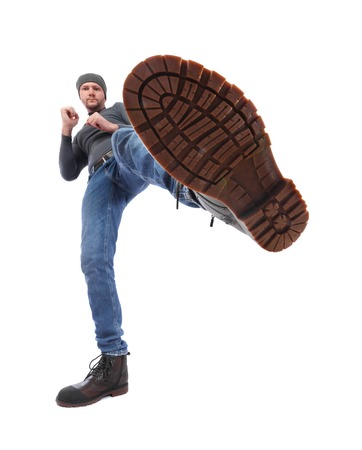 Foto de The man is kicking. Foot with a shoe close-up. Corrugated sole of the boot from the bottom up - Imagen libre de derechos