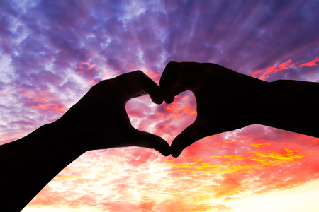 Photo pour Silhouette hand in heart shape and beautiful sky - image libre de droit