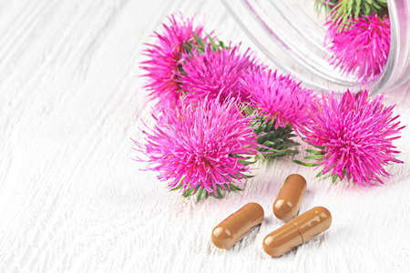 Photo for Silybum marianum (milk thistle) pills and flowers on a white wooden table (selective focus).One of the most common uses of milk thistle is to treat liver problems - Royalty Free Image