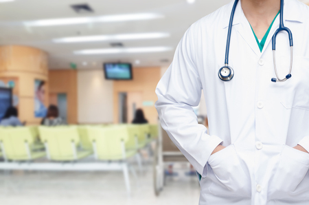 Photo pour smart doctor with a stethoscope around his neck with blurred image of people waiting at hospital background, healthcare medical technology concept, copy space, color effect tone - image libre de droit