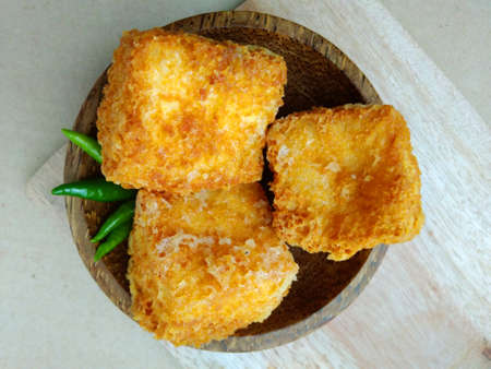 Foto per flat lays or top view, tahu sumedang (Fried Tofu) from west java,  indonesia with green hot chili at Wooden small bowl - Immagine Royalty Free