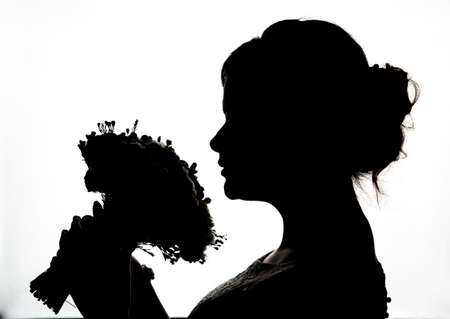 Photo for Young bride silhouette  with wedding bouquet on a white background - Royalty Free Image