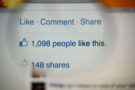 Photo pour LISBON, PORTUGAL - AUGUST 27, 2014: Photo of Facebook notifications of Likes and Shares on a monitor screen through a magnifying glass. - image libre de droit