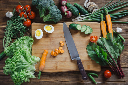 Photo pour Healthy food and ingredients with tomato, salad, arugula, carrots, beet, beetroot, leaves, cucumber, onion, green, radish, mushrooms, garlic, broccoli, half, egg and peas on rustic wooden background, top view - image libre de droit