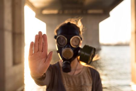 Foto de Ecological concept of air contamination. Woman in gas mask near water showing stop gesture - Imagen libre de derechos