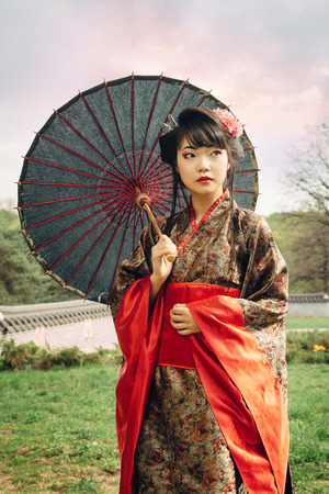 Foto de Beautiful asian woman walking in the garden and wearing traditional japanese kimono and traditional umbrella - Imagen libre de derechos