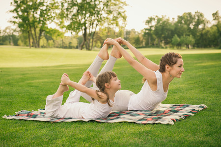 Photo pour Young mother and daughter doing gymnastics and stretching in the city park on sunset - image libre de droit
