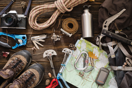 Foto de Equipment necessary for mountaineering and hiking on wooden background - Imagen libre de derechos