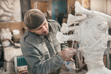 Photo for Sculptor man сreating sculpture from plaster and clay in his workshop - Royalty Free Image