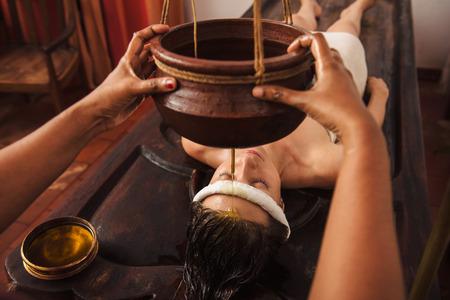 Photo pour Caucasian woman having Ayurveda shirodhara treatment in India - image libre de droit