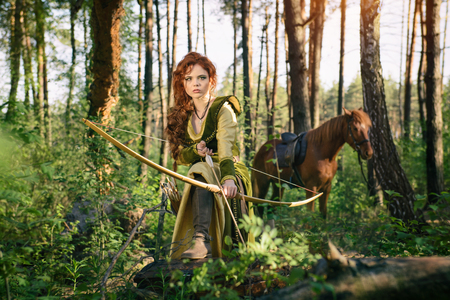 Photo for Warrior medieval woman with bow hunting in mystery forest - Royalty Free Image