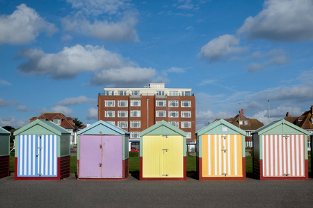 Photo for Brighton seafront five beach huts, with multi coloured doors of yellow, pink, black stripes behind is an appartment building and blue sky - Royalty Free Image
